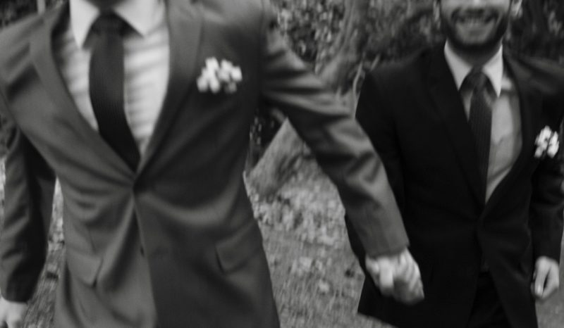 Two men in suits holding hands