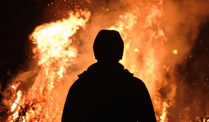 Silhouette with fire behind