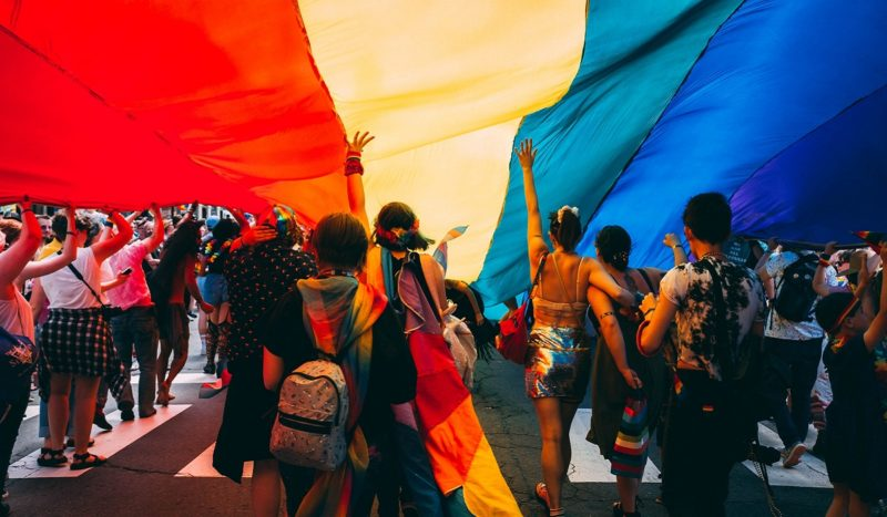 Running in street with LGBTQ Pride flag